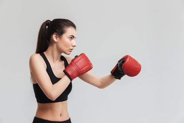 회색 벽에 격리된 아름다운 젊은 스포츠 피트니스 여성 복서의 이미지는 장갑을 끼고 운동을 합니다.