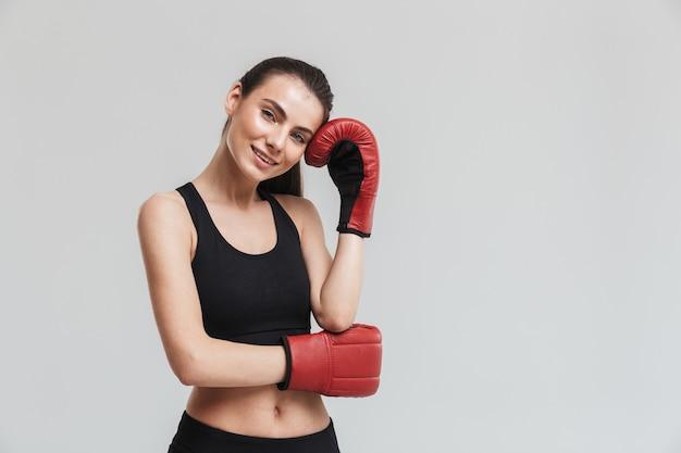 灰色の壁に隔離された美しい若いスポーツフィットネス女性ボクサーの画像は、手袋でエクササイズをします。