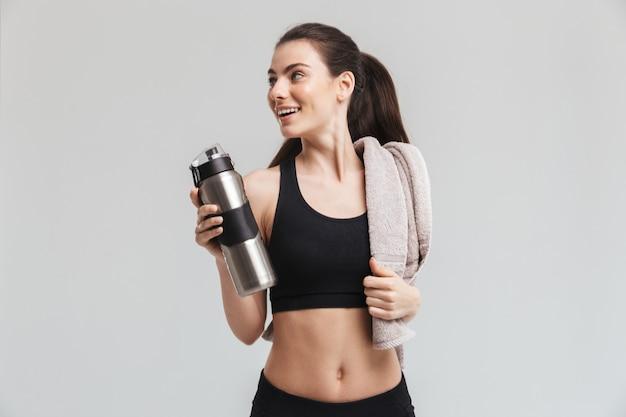 灰色の壁に隔離された水を飲む美しい若いスポーツフィットネス女性の画像。