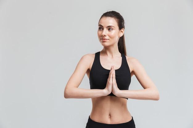 Изображение красивой молодой женщины фитнеса спорта делает упражнения изолированными над медитацией серой стены.