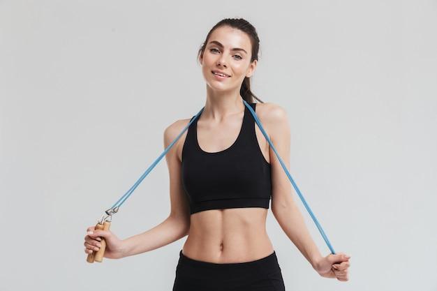 아름다운 젊은 스포츠 피트니스 여성의 이미지는 회색 벽에 격리된 장비로 운동을 합니다.