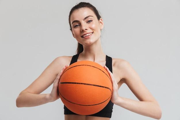 Изображение игрока женщины фитнеса красивого молодого спорта делает упражнения играть в баскетбол изолированными над серой стеной.