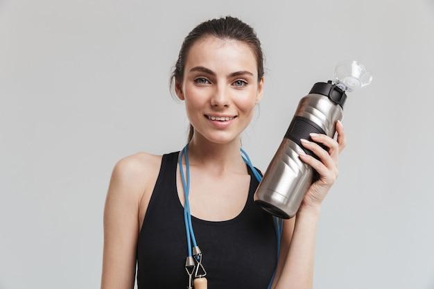 水でボトルを保持している灰色の壁の上に分離された縄跳びでポーズをとってポーズをとる美しい若いスポーツフィットネス女性の画像。
