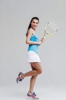 美しい若いスポーツフィットネスの女性テニスプレーヤーの画像は、灰色の壁に隔離されたエクササイズを行います。