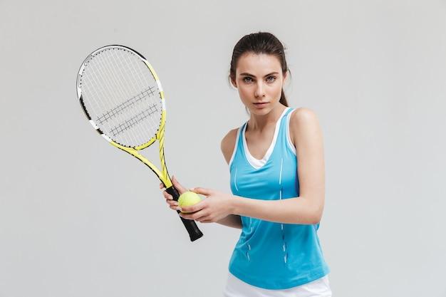 아름다운 젊은 스포츠 피트니스 여성 테니스 선수의 이미지는 회색 벽에 격리된 운동을 합니다.