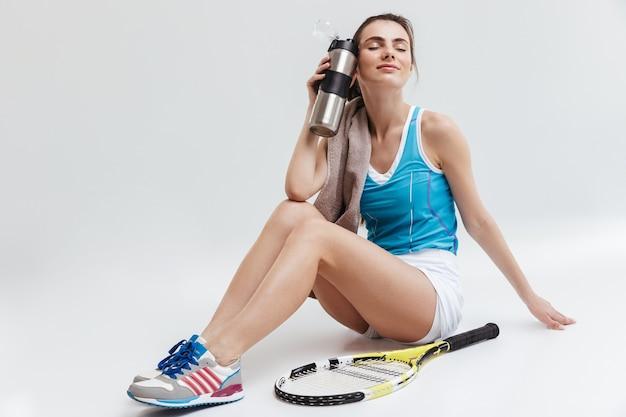 灰色の壁に孤立してポーズをとる美しい若いスポーツフィットネス女性テニスプレーヤーの画像。