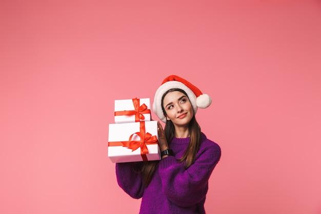 クリスマスの帽子をかぶってギフトボックスを保持しているピンクの上に孤立してポーズをとってポーズをとる美しい若い思考の女性の画像。