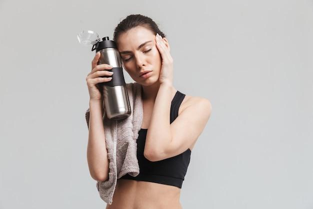 灰色の壁に隔離された水とタオルとボトルでポーズをとる美しい若い疲れたスポーツフィットネス女性の画像。
