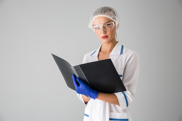 フォルダーを保持している灰色の壁の上に隔離された美しい若い女性の美容師の医師の画像。