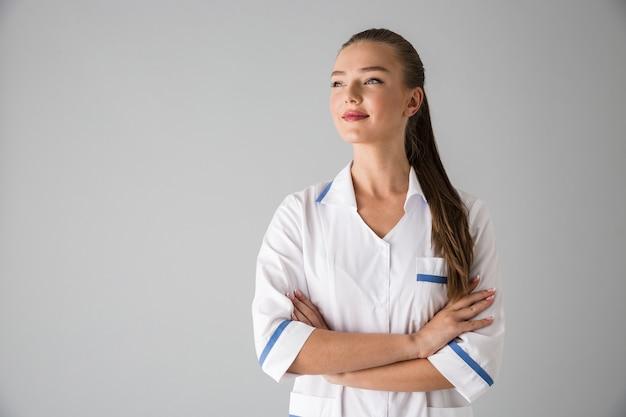 회색 벽 위에 절연 아름 다운 젊은 여자 미용사 의사의 이미지.