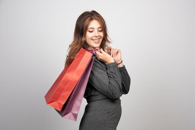 ショッピングバッグを保持している灰色の壁の上に孤立してポーズをとってポーズをとる美しい若い女性の画像。