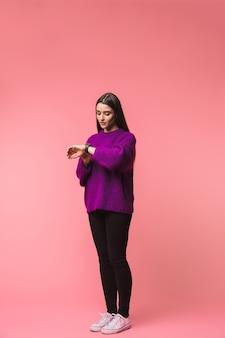 時計を見てピンクの空間に孤立してポーズをとる美しい若い女性の画像。