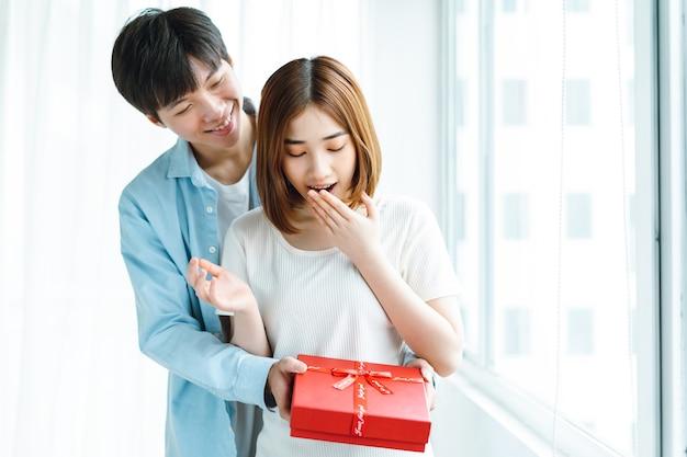 バレンタインデーにガールフレンドにプレゼントを贈る彼氏の画像