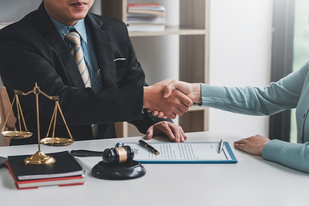 女性クライアントのコラボレーション契約書と机に置かれた木槌と握手するビジネスマンの弁護士の画像。