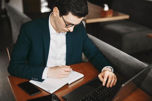 Изображение кавказского бизнесмена работая во время работы портативного компьютера и делая заметки.