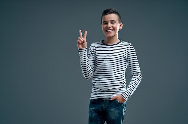 平和のジェスチャーを示す灰色の壁の上に孤立してポーズをとる陽気な楽観的な前向きな少年の子供の画像。