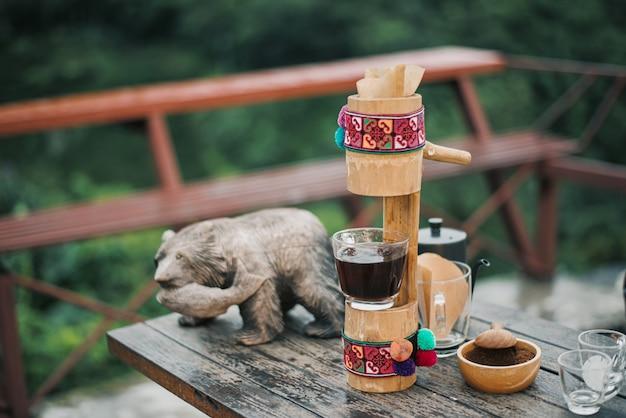 新鮮なコーヒー豆を背景に竹で作られたコーヒーマシンの画像。