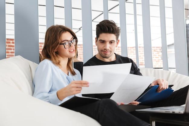 Изображение концентрированной молодой влюбленной пары дома в помещении с помощью портативного компьютера работы с документами.