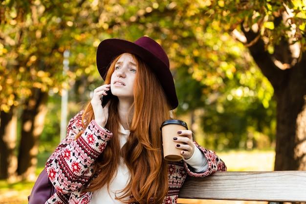 コーヒーを飲みながら携帯電話で話している秋の公園で混乱している悲しい若い学生赤毛の女の子の画像。