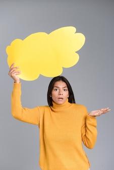 Изображение запутанной женщины, позирующей изолированной над серой стеной, держащей пузырь мысли.