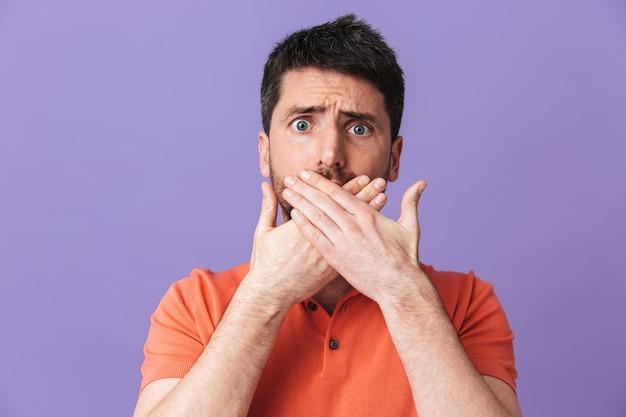 Изображение сбитого с толку молодого красивого бородатого мужчины, позирующего изолированно над фиолетовой стеной, закрывающей рот руками.