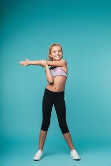 Изображение милой маленькой девочки делает упражнения фитнеса изолированными над голубой стеной.