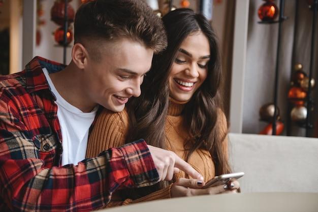 Изображение милой молодой влюбленной пары, сидящей в кафе в помещении с помощью мобильного телефона.