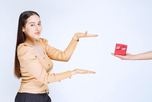 Изображение милой молодой женщины стоя и показывая большой размер руками.