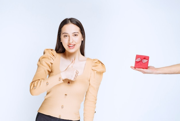 Изображение милой молодой женщины стоя и показывая большой палец вверх.