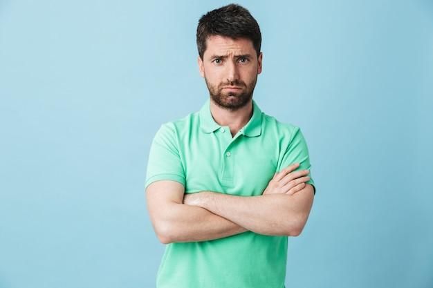 Изображение недовольного молодого красивого бородатого мужчины, позирующего изолированно над синей стеной.
