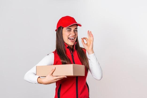 小包ポストボックスと立っている赤い帽子で興奮して幸せな若い配達女性の画像
