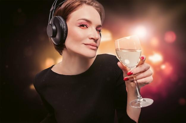 Изображение девушки в черном платье с бокалом вина в руке в ночном клубе. профессиональные наушники. концепция партии. смешанная техника