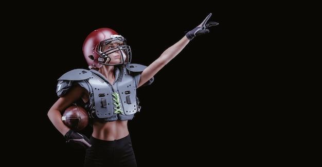 미식축구팀 선수의 유니폼을 입은 소녀의 이미지. 그녀는 빈 곳을 가리킵니다. 검은 배경. 스포츠 개념입니다. 어깨 패드. 혼합 매체