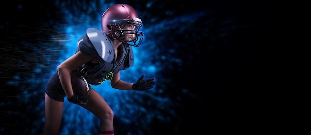 미식축구팀 선수의 유니폼을 입은 소녀의 이미지. 그녀는 밝은 반점을 배경으로 공을 가지고 달린다. 스포츠 개념입니다. 어깨 패드. 혼합 매체