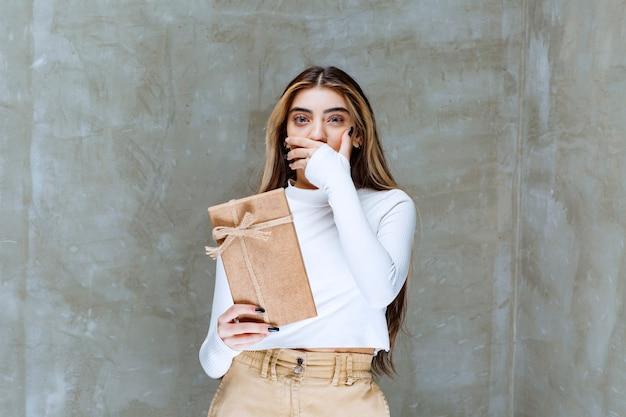石の上に存在する紙を保持している女の子モデルの画像
