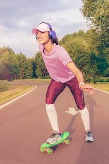 Изображение девушки на скейтборде в парке. спортивная концепция. смешанная техника