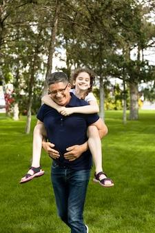 姪っ子を肩に抱えた祖父の姿で、自然の中で楽しい一日を過ごしています。一緒に楽しい時間を過ごしましょう。