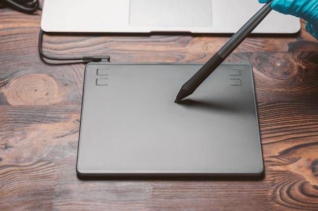 나무 테이블에 그래픽 태블릿, 스타일러스 및 노트북의 이미지. 디자이너 직장입니다. 프리랜서. 리터칭. it 개념입니다. 혼합 매체
