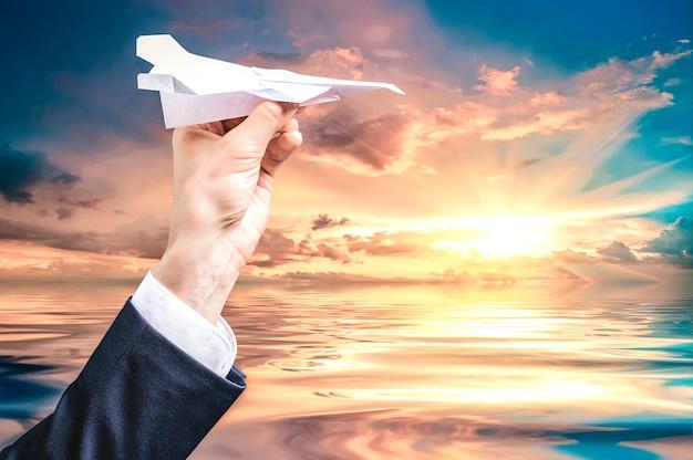 Изображение руки, держащей бумажный самолетик. концепция туризма. смешанная техника