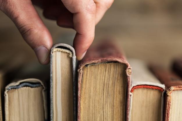 오래된 책을 선택하는 손 이미지