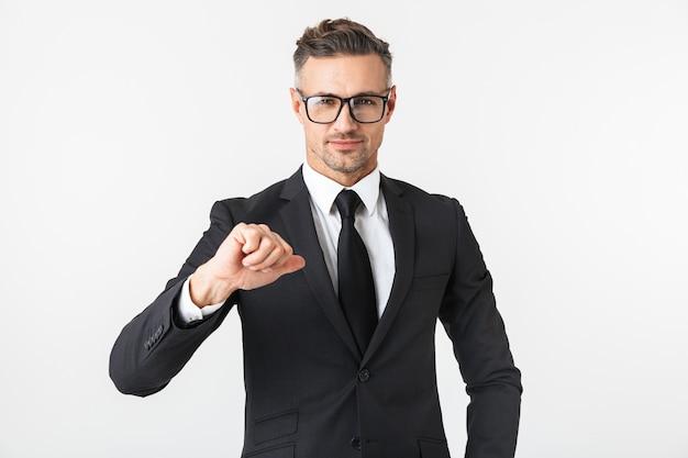 時計の時計を見てポーズをとって白い壁に隔離されたハンサムなビジネスマンの画像。