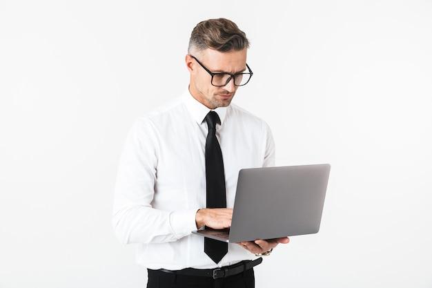 Изображение красивого делового человека, изолированного над белой стеной, с помощью портативного компьютера.
