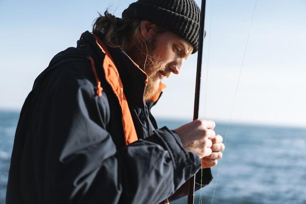 海岸でコートと帽子をかぶっているハンサムな集中した若い男の漁師の画像。