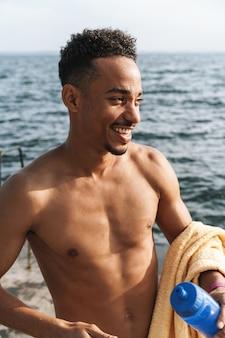 ビーチの海で屋外タオルを持っているハンサムな幸せな陽気な若いアフリカのスポーツマンの画像。