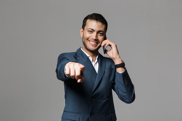 Изображение красивого счастливого улыбающегося молодого делового человека, изолированного над серой стеной, разговаривает по мобильному телефону, указывая на вас.