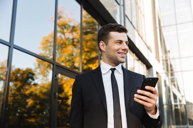 Изображение красивого счастливого молодого бизнесмена, прогулки на открытом воздухе возле бизнес-центра с помощью мобильного телефона.