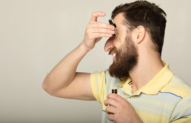Изображение красивого мужчины с пипеткой с маслом для бороды