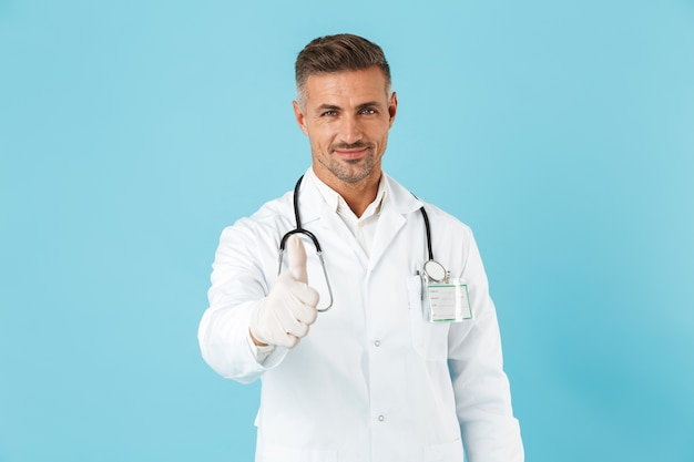 엄지 손가락을 보여주는 파란색 벽 벽 위에 절연 포즈 잘 생긴 성숙한 남자 의사의 이미지.