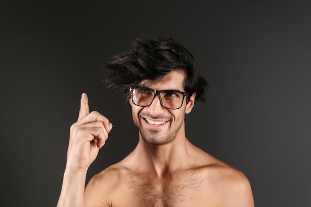 Изображение красивого обнаженного молодого улыбающегося человека, позирующего изолированно в очках, указывая.