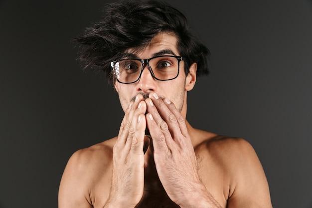 Изображение красивого потрясенного эмоционального молодого человека, позирующего изолированно в очках.